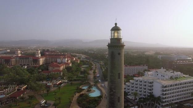 Аэрофотоснимок курортного города на побережье гран-канарии с маяком маспаломас на переднем плане