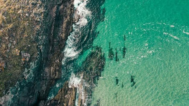 청록색 바다 근처 바위 절벽의 항공 샷