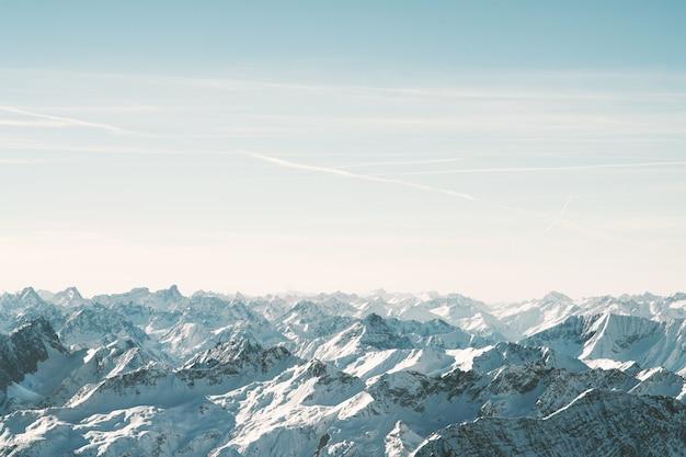 Воздушный выстрел из снежных гор под красивым небом в дневное время