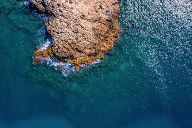 イタリア、ポリニャーノアマーレの日光の下でのアドリア海と岩の空中ショット