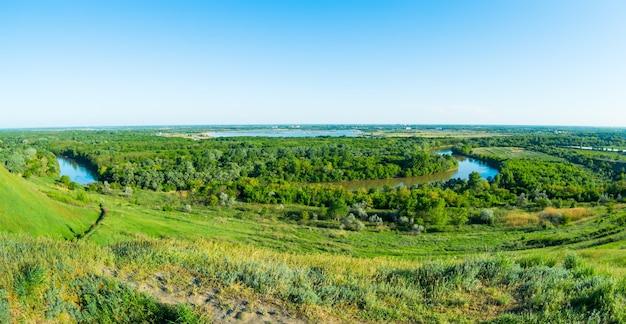 クラスノダール地方、ロシア、クバン川の緑の丘に囲まれた美しいロシアの川の空中ショット。