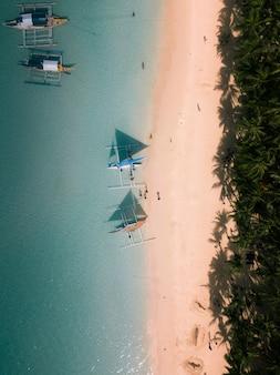 穏やかな透き通った海でのボートの空中ショット
