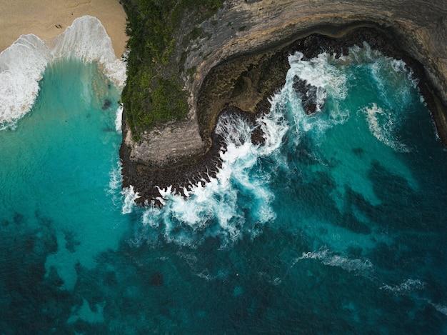 바다로 둘러싸인 녹지로 덮인 절벽의 공중 촬영