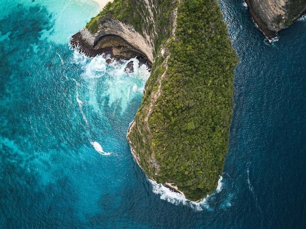 海に囲まれた緑に覆われた崖の空中ショット