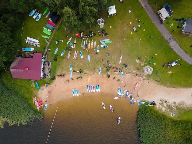 人々がsupスタンドアップパドルボードで漕ぐ夏の日のドローンからの湖の空中ショット