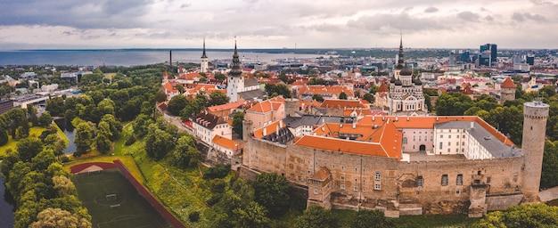 オレンジ色の屋根、教会の尖塔、狭い通りのあるタリンの旧市街の空中ショット