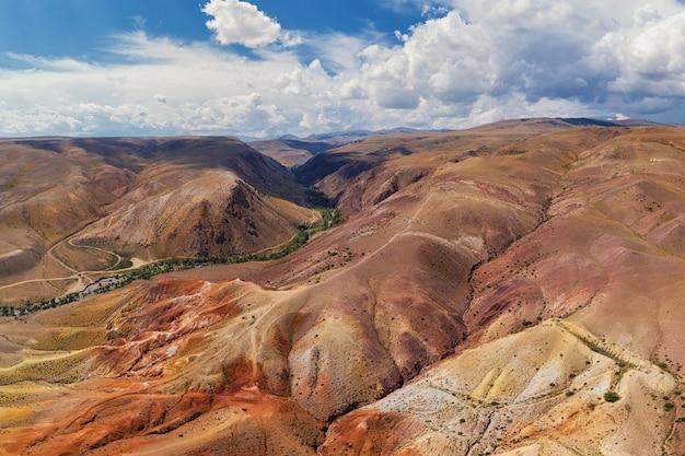 Аэрофотоснимок текстурированных желтых и красных гор, напоминающих поверхность марса.