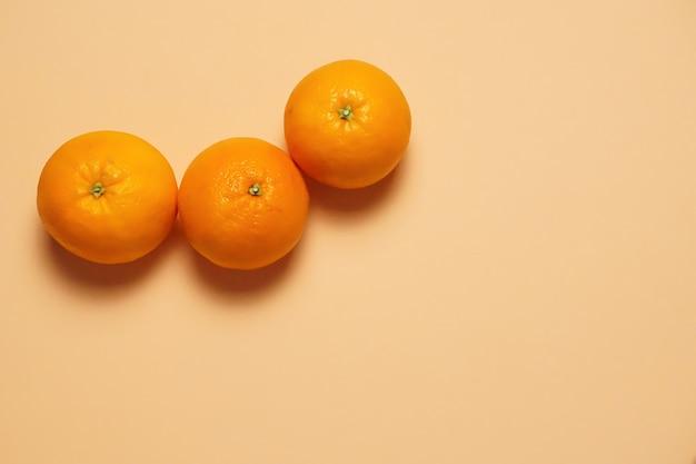 백그라운드에서 오렌지 색상으로 세 가지 맛있는 오렌지 과일의 공중 샷