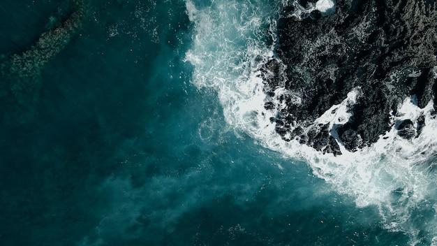 ハワイの溶岩の岩の海岸に衝突する波の空中ショット