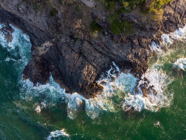 Воздушная съемка волн, падающих на скалу