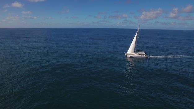 Воздушная съемка белой яхты, плывущей в синем океане. путешествие по воде