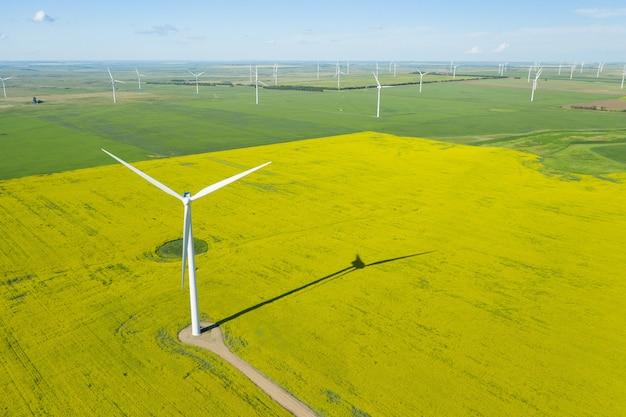 昼間の広いフィールドでの風力発電機の空中ショット