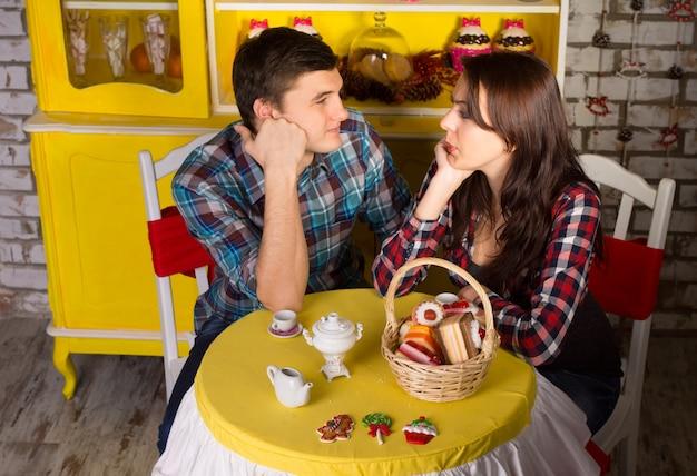 カフェショップでデートしながら顔に手を当ててお互いを見て、市松模様のトップスで若いカップルの空中ショット