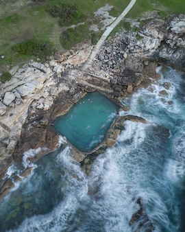 Aerial shot of people swimming in a large pool built on the rocky coast in thailand