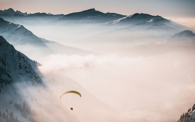 Aerial shot of a person parachuting down above the clouds near snowy mountains