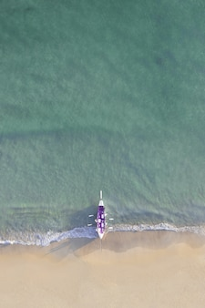 Aerial shot of a purple boat on a beautiful shore under the sunlight