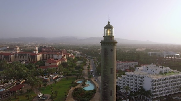 Aerial shot of resort town on the coast of gran canaria with maspalomas lighthouse in foreground