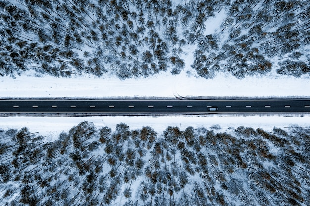 Aerial shot of a road in a forest covered in the snow during winter
