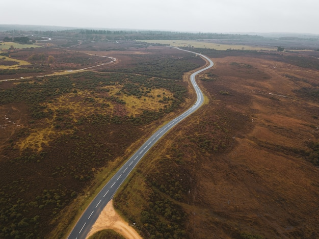 Aerial shot of a road in the middle of a green landscape in the new forest, near brockenhurst, uk