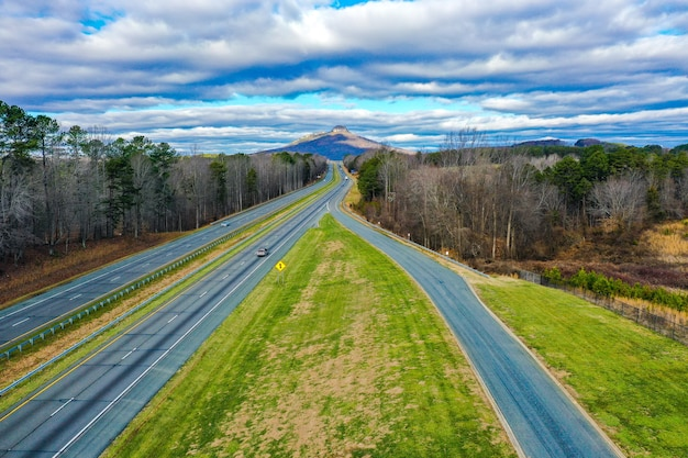 Aerial shot of a road with pilot mountain in north carolina, usa and a cloudy blue sky