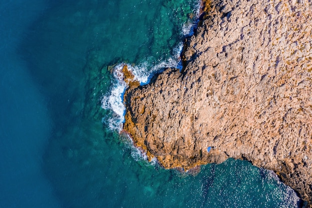 Aerial shot of a rocky cliff surrounded by the sea