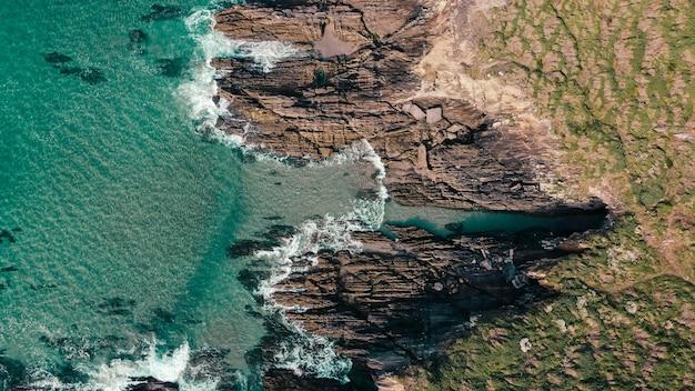 Ripresa aerea di scogliere rocciose vicino a un paesaggio marino turchese