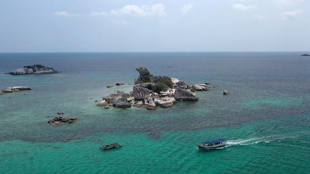 Ripresa aerea di un'isola rocciosa vicino a una barca in mare
