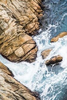 Aerial shot of sea waves hitting the rocks