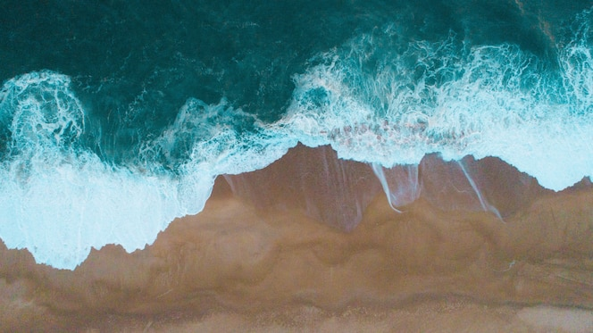 Aerial shot of sea waves hitting the sandy shore