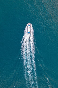 Aerial shot of the sea with a motorboat crossing it and leaving a white trace