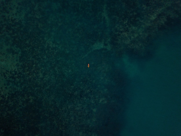 Aerial shot of the sea with a small kayak visible in the distance