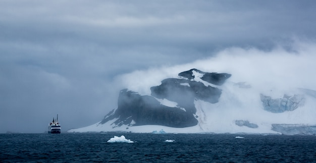 Aerial shot of a ship and iceberg in antarctica under cloudy sky