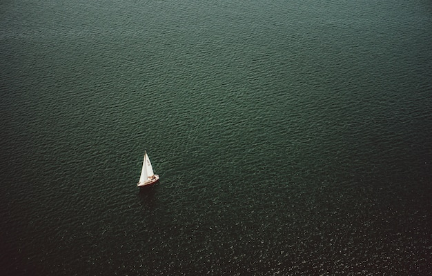 Aerial shot of a small boat sailing in the wide beautiful ocean