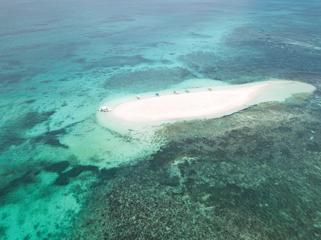 Aerial shot of a small sandy island surrounded by water with a few boats