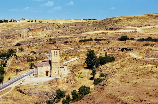 Ripresa aerea di una piccola torre accanto a una strada nella valle gialla a segovia, spagna