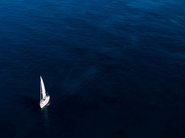 Aerial shot of a small white boat sailing in the ocean