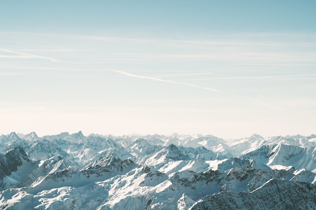 Aerial shot of snowy mountains under a beautiful sky at daytime
