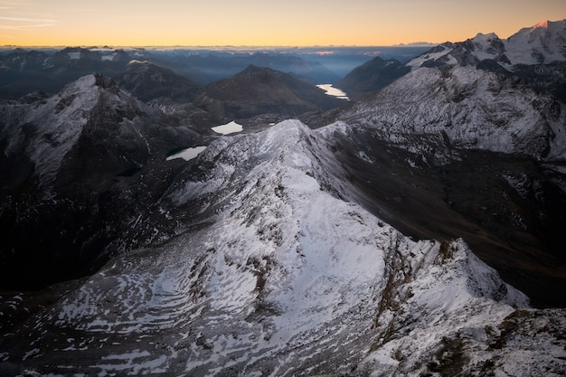 Aerial shot of snowy mountains with a clear sky