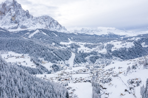 Aerial shot of a town in winter surrounded by mountains