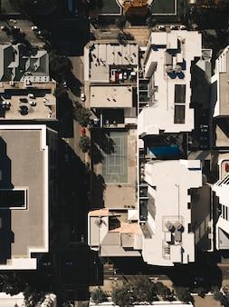 Ripresa aerea di una città con edifici alti e un campo da tennis
