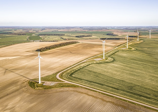 Aerial shot of the turbines on the beautiful green fields near the plowed farms