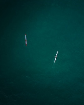 Aerial shot of two kayaks cruising in the open sea