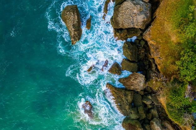 Ripresa aerea di un mare ondoso contro le scogliere ricoperte di verde