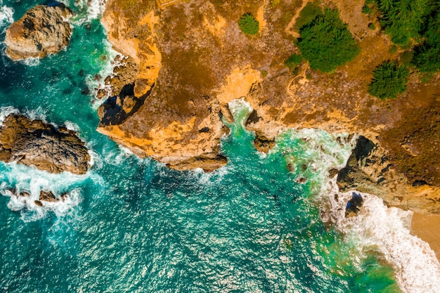 Aerial shot of a wavy sea against the cliffs at daytime