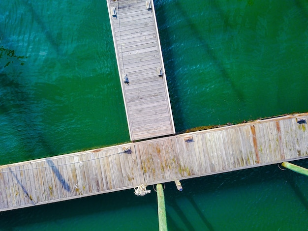 Aerial shot of a wooden pier with ropes on the dock