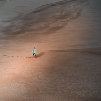 Aerial shot young woman holding a surfboard walking in an empty desert leaving her foot traces