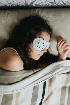 A aerial shot of a young woman sleeping on the bed with a white sleeping mask