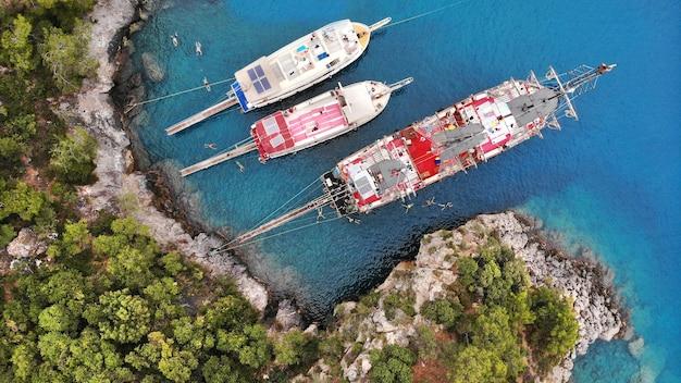 Антенна. экскурсионные корабли и туристы, купающиеся в бирюзовом море. вид сверху с дрона.