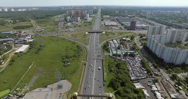 忙しい高速道路のある空中夏の街並み。巡回交通のあるインターチェンジ上空を飛行するヘリコプター。ロシアのモスクワ