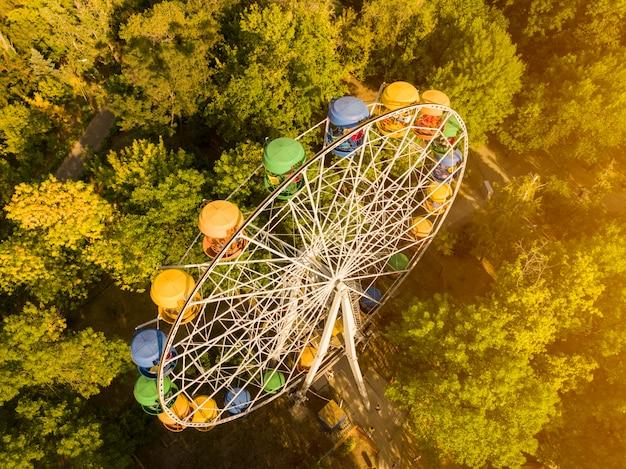 Воздушная вершина прямо над колесом обозрения в летнем городском парке развлечений, беспилотный выстрел d